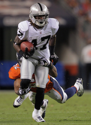 DENVER, CO - SEPTEMBER 12:  Wide receiver Denarius Moore #17 of the Oakland Raiders makes a reception as linbacker Jason Hunter #52 of the Denver Broncos makes the tackle at Sports Authority Field at Mile High on September 12, 2011 in Denver, Colorado.  (