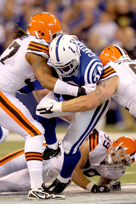 INDIANAPOLIS, IN - SEPTEMBER 18:  Delone Carter #34 of the Indianapolis Colts is tackled by Jabaal Sheard #97 and  #91 of the Cleveland Browns at Lucas Oil Stadium on September 18, 2011 in Indianapolis, Indiana.  (Photo by Matthew Stockman/Getty Images)