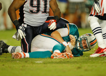 MIAMI GARDENS, FL - SEPTEMBER 12:  Chad Henne #7 of the Miami Dolphins is sacked during a game against the New England Patriots at Sun Life Stadium on September 12, 2011 in Miami Gardens, Florida.  (Photo by Mike Ehrmann/Getty Images)