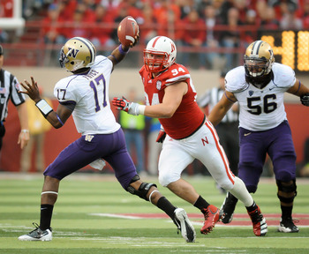 LINCOLN, NE - SEPTEMBER 17: Keith Price #17 of the Washington Huskies gets rid of the ball before taking a hit from Jared Crick #94 of the Nebraska Cornhuskers during their game at Memorial Stadium September 17, 2011 in Lincoln, Nebraska. Nebraska won 51-