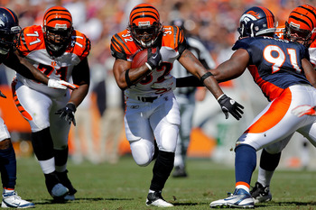 DENVER, CO - SEPTEMBER 18:  Running Back Cedric Benson #32 of the Cincinnati Bengals runs with the ball past defensive end Robert Ayers #91 of the Denver Broncos at Sports Authority Field at Mile High on September 18, 2011 in Denver, Colorado. (Photo by J