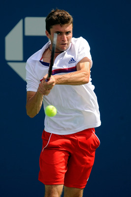 NEW YORK, NY - SEPTEMBER 08:  Gilles Simon of France returns a shot against John Isner of the United States during Day Eleven of the 2011 US Open at the USTA Billie Jean King National Tennis Center on September 8, 2011 in the Flushing neighborhood of the