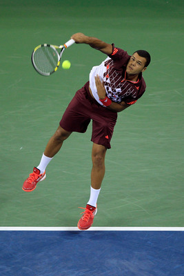 NEW YORK, NY - SEPTEMBER 08:  Jo-Wilfried Tsonga of France serves against Roger Federer of Switzerland during Day Eleven of the 2011 US Open at the USTA Billie Jean King National Tennis Center on September 8, 2011 in the Flushing neighborhood of the Queen