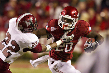 FAYETTEVILLE, AR - SEPTEMBER 17:  Ronnie Wingo Jr. #20 of the Arkansas Razorbacks stiff arms  Angelo Hadley #22 of the Troy Trojans at Donald W. Reynolds Razorback Stadium on September 17, 2011 in Fayetteville, Arkansas.  The Razorbacks beat the Trojans 3
