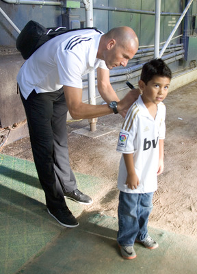 SAN DIEGO, CA - JULY 20:  Technical Assistant  Zinedine Zidane of Real Madrid signs an autograph for a fan prior to the game against CD Guadalajara at Qualcomm Stadium on July 20, 2011 in San Diego, California. (Photo by Kent Horner/Getty Images)