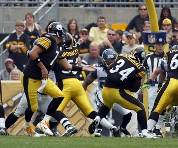 PITTSBURGH, PA - SEPTEMBER 18:   Ben Roethlisberger #7 of the Pittsburgh Steelers hands the ball off to Rashard Mendenhall #34 for a touchdown against the Seattle Seahawks during the game on September 18, 2011 at Heinz Field in Pittsburgh, Pennsylvania.