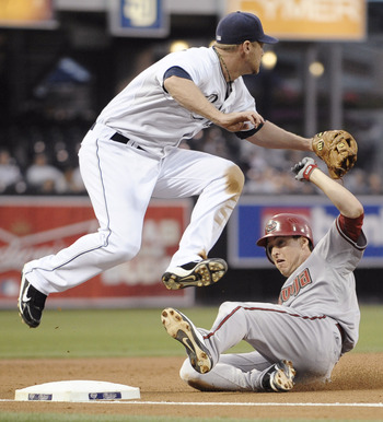 SAN DIEGO, CA - JULY 26: Chase Headley #7 of the San Diego Padres jumps over Kelly Johnson #2 of the Arizona Diamondbacks as Johnson slides into third base with a triple during the third inning of a baseball game at Petco Park on July 26, 2011 in San Dieg