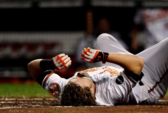BALTIMORE, MD - SEPTEMBER 17: Mark Reynolds #12 of the Baltimore Orioles lays in the first after getting hit by a pitch in the head against the Los Angeles Angels of Anaheim in the third inning at Oriole Park at Camden Yards on September 17, 2011 in Balti