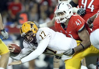 TUCSON, AZ - DECEMBER 02:  Quarterback Brock Osweiler #17 of the Arizona State Sun Devils drives with the football for a first down past Paul Vassallo #41 of the Arizona Wildcats during the college football game at Arizona Stadium on December 2, 2010 in T
