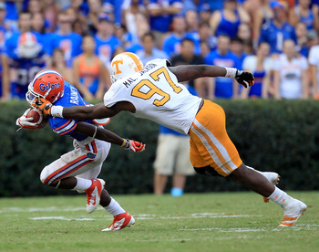 GAINESVILLE, FL - SEPTEMBER 17:  Running back Chris Rainey #1 of the Florida Gators has his facemask grabbed by defensive lineman Malik Jackson #97 of the Tennessee Volunteers during a game at Ben Hill Griffin Stadium on September 17, 2011 in Gainesville,