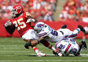 KANSAS CITY, MO - SEPTEMBER 11:  Jamall Charles #25 of the Kansas City Chiefs is tackled by Nick Barnett #50 and Aaron Williams #23 of the Buffalo Bills during the game at Arrowhead Stadium on September 11, 2011 in Kansas City, Missouri.  (Photo by Jamie