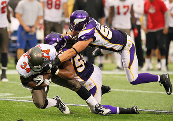 MINNEAPOLIS, MN - SEPTEMBER 18:  (L-R)  Earnest Graham #34 of the Tampa Bay Buccaneers gets stopped by  E.J. Henderson #56 and  Chad Greenway #52 of the Minnesota Vikings at the Hubert H. Humphrey Metrodome on September 18, 2011 in Minneapolis, Minnesota.