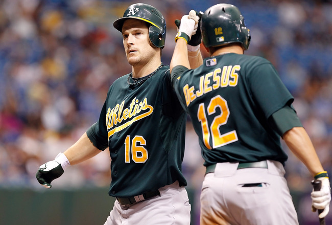 ST. PETERSBURG, FL - AUGUST 07:  Outfielder Josh Willingham #16 of the Oakland Athletics is congratulated by David DeJesus #12 after his home run against the Tampa Bay Rays during the game at Tropicana Field on August 7, 2011 in St. Petersburg, Florida.