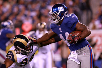 EAST RUTHERFORD, NJ - SEPTEMBER 19:  Ahmad Bradshaw #44 of the New York Giants runs the ball against Robert Quinn #94 of the St. Louis Rams at MetLife Stadium on September 19, 2011 in East Rutherford, New Jersey.  (Photo by Nick Laham/Getty Images)