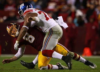 LANDOVER, MD - JANUARY 02:  Quarterback Rex Grossman #5 of the Washington Redskins is hit by defensive end Osi Umenyiora #72 of the New York Giants at FedEx Field on January 2, 2011 in Landover, Maryland. The Giants won the game 17-14.  (Photo by Win McNa