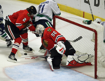 CHICAGO, IL - APRIL 24: Corey Crawford #50 of the Chicago Blackhawks knocks the puck between the legs of teammate Duncan Keith #2 against the Vancouver Canucks in Game Six of the Western Conference Quarterfinals during the 2011 NHL Stanley Cup Playoffs at