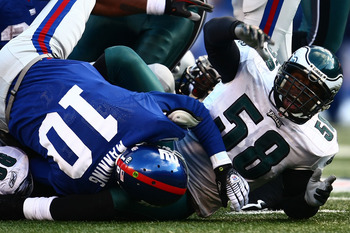 EAST RUTHERFORD, NJ - JANUARY 11:  Trent Cole #58 of the Philadelphia Eagles reacts after stopping Eli Manning #10 of the New York Giants on fourth down during the NFC Divisional Playoff Game on January 11, 2009 at Giants Stadium in East Rutherford, New J