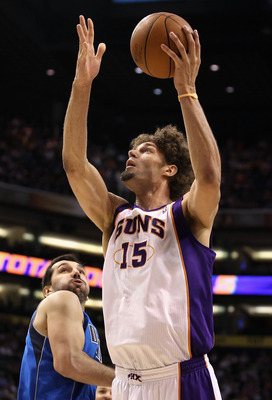 PHOENIX, AZ - FEBRUARY 17:  Robin Lopez #15 of the Phoenix Suns puts up a shot past Peja Stojakovic #16 of the Dallas Mavericks during the NBA game at US Airways Center on February 17, 2011 in Phoenix, Arizona.  NOTE TO USER: User expressly acknowledges a
