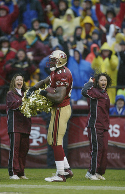 SAN FRANCISCO - DECEMBER 15:  Wide receiver Terrell Owens #81 of the San Francisco 49ers celebrates with a cheerleader's pom poms after scoring a touchdown against the Green Bay Packers during the NFL game at 3Com Park on December 15, 2002 in San Francisc