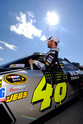JOLIET, IL - SEPTEMBER 17:  Jimmie Johnson, driver of the #48 Lowe's/Kobalt Tools Chevrolet, climbs out of his car after qualifying for the NASCAR Sprint Cup Series GEICO 400 at Chicagoland Speedway on September 17, 2011 in Joliet, Illinois.  (Photo by Ja