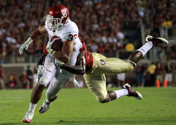 TALLAHASSEE, FL - SEPTEMBER 17: Trey Millard #33 of the Oklahoma Sooners is tackled by Nigel Bradham #13 of the Florida State Seminoles at Doak Campbell Stadium on September 17, 2011 in Tallahassee, Florida.  (Photo by Ronald Martinez/Getty Images)