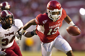 FAYETTEVILLE, AR - SEPTEMBER 17:  Javontee Herndon #19 of the Arkansas Razorbacks is grabbed from behind by Ethan Davis #34 of the Troy Trojans at Donald W. Reynolds Razorback Stadium on September 17, 2011 in Fayetteville, Arkansas.  The Razorbacks beat t