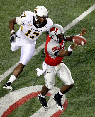 LAS VEGAS - NOVEMBER 13:  Quarterback Omar Clayton #2 of the UNLV Rebels throws under pressure from Keith Lewis #17 of the Wyoming Cowboys during their game at Sam Boyd Stadium November 13, 2010 in Las Vegas, Nevada. UNLV won 42-16.  (Photo by Ethan Mille