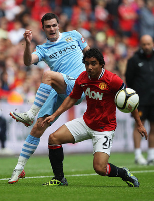 LONDON, ENGLAND - AUGUST 07:  Adam Johnson of Manchester City and Rafael Da Silva of Manchester United battle for the ball during the FA Community Shield match sponsored by McDonald's between Manchester City and Manchester United at Wembley Stadium on Aug
