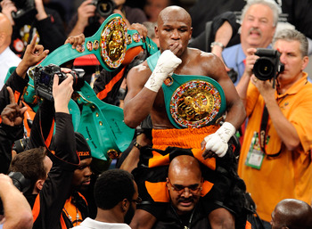 LAS VEGAS, NV - SEPTEMBER 17:  Floyd Mayweather Jr. is carried in the ring by CEO of Mayweather Promotions Leonard Ellerbe as they celebrate Mayweather's fourth-round knockout of Victor Ortiz to win the WBC welterweight title September 17, 2011 in Las Veg