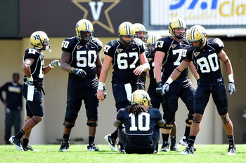 NASHVILLE, TN - SEPTEMBER 17:  Players gather around teammate Larry Smith #10 of the Vanderbilt Commodores after he was injured playing against the Ole Miss Rebels at Vanderbilt Stadium on September 17, 2011 in Nashville, Tennessee. Vnderbilt won 30-7.  (