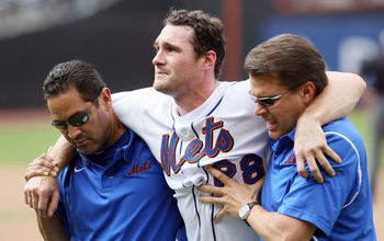 NEW YORK, NY - AUGUST 07:  Daniel Murphy #28 of the New York Mets is helped off the field by head trainer Ray Ramirez (L) and trainer Mike Herbst after a seventh inning injury trying to prevent a stolen base against the Atlanta Braves at Citi Field on Aug