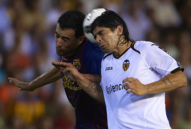 VALENCIA, SPAIN - SEPTEMBER 21:  Ever Banega (R) of Valencia duels for the ball with Sergio Busquets of Barcelona during the La Liga match between Valencia and Barcelona at Estadio Mestalla on September 21, 2011 in Valencia, Spain.  (Photo by Manuel Queim