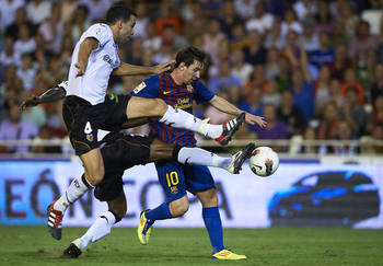VALENCIA, SPAIN - SEPTEMBER 21:  Miguel Brito (L) and Adil Rami of Valencia duels for the ball with Lionel Messi of Barcelona during the La Liga match between Valencia and Barcelona at Estadio Mestalla on September 21, 2011 in Valencia, Spain.  (Photo by
