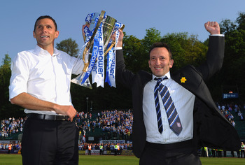 BRIGHTON, ENGLAND - APRIL 30:  Brighton manager Gus Poyet (L) and chairman Tony Bloom hold aloft the Division One trophy after the npower League One match between Brighton & Hove Albion and Huddersfield Town at Withdean Stadium on April 30, 2011 in Bright