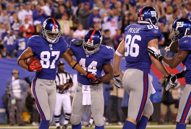 EAST RUTHERFORD, NJ - SEPTEMBER 19:  Domenik Hixon #87 of the New York Giants favors his leg as he is assisted by teammate Ahmad Bradshaw #44 after Hixon scored a touchdown reception against the St. Louis Rams at MetLife Stadium on September 19, 2011 in E