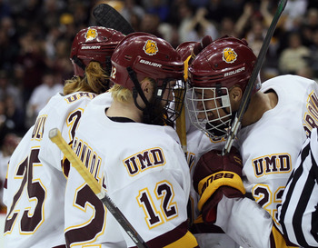 ST. PAUL, MN - APRIL 07:  Jack Connolly #12 of the Minnesota Duluth Bulldogs is congratulated by teammate J.T. Brown #23 after Connolly scored in the second period against the Notre Dame Fighting Irish during semifinals of the 2011 NCAA Men's Frozen Four