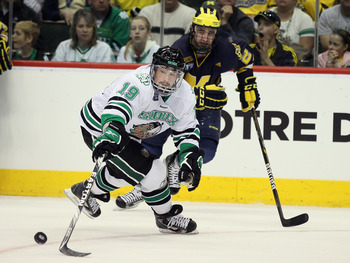 ST. PAUL, MN - APRIL 07:  Evan Trupp #19 of the North Dakota Fighting Sioux tries to keep the puck as Jeff Rohrkemper #22 of the Michigan Wolverines defends during semifinals of the 2011 NCAA Men's Frozen Four on April 7, 2011 at the Xcel Energy Center in