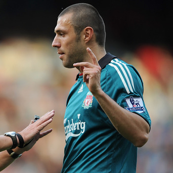LONDON, ENGLAND - MAY 09:  Referee Alan Wiley discusses a decision with Andrea Dossena of Liverpool during the Barclays Premier League match between West Ham United and Liverpool at Upton Park on May 9, 2009 in London, England.  (Photo by Shaun Botterill/
