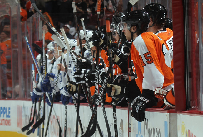 PHILADELPHIA, PA - SEPTEMBER 21: Players tap their sticks on the boards to salute Jay Rosehill #38 of the Toronto Maple Leafs and Jody Shelley #45 of the Philadelphia Flyers following their second period fight at the Wells Fargo Center on September 21, 20