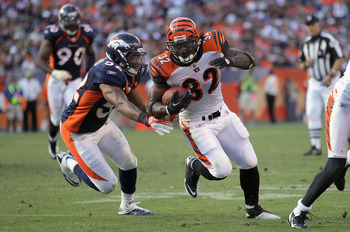DENVER, CO - SEPTEMBER 18:  Cedric Benson #32 of the Cincinnati Bengals rushes with the ball as Wesley Woodyard #52 of the Denver Broncos mkaes the tackle at Invesco Field at Mile High on September 18, 2011 in Denver, Colorado. The Broncos defeated the Be
