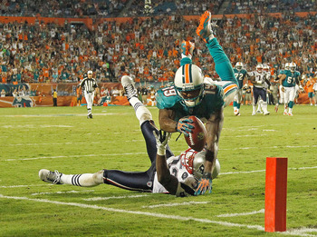 MIAMI GARDENS, FL - SEPTEMBER 12:  Brandon Marshall #19 of the Miami Dolphins scores a touchdown over  Devin McCourty #32 of the New England Patriots during a game  at Sun Life Stadium on September 12, 2011 in Miami Gardens, Florida.  (Photo by Mike Ehrma