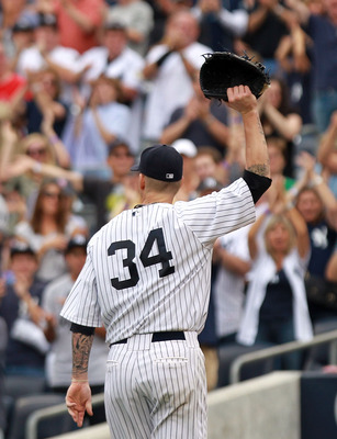 NEW YORK, NY - SEPTEMBER 25:  A.J. Burnett #34 of the New York Yankees salutes the crowd as he leaves the game in the eighth inning against the Boston Red Sox on September 25, 2011 at Yankee Stadium in the Bronx borough of New York City.  (Photo by Nick L