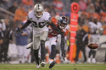 DENVER, CO - SEPTEMBER 12:  Wide receiver  Brandon Lloyd #84 of the Denver Broncos and cornerback Stanford Routt #26 of the Oakland Raiders vie for the ball in the rain at Sports Authority Field at Mile High on September 12, 2011 in Denver, Colorado.  (Ph