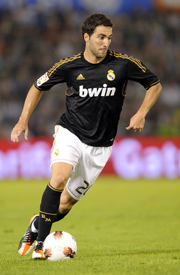 SANTANDER - SEPTEMBER 21:  Gonzalo Higuain of Real Madrid runs with the ball during the La Liga soccer match between Real Racing Club and Real Madrid at El Sardinero Stadium on September 21, 2011 in Santander, Spain. (Photo by Victor Fraile/Getty Images)