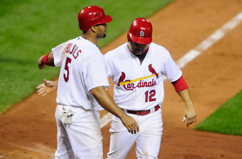 ST. LOUIS, MO - SEPTEMBER 20: Albert Pujols #5 and Lance Berkman #12 of the St. Louis Cardinals celebrate after scoring against the New York Mets at Busch Stadium on September 20, 2011 in St. Louis, Missouri.  (Photo by Jeff Curry/Getty Images)
