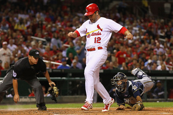 ST. LOUIS, MO -SEPTEMBER 7: Lance Berkman #12 of the St. Louis Cardinals scores a run against Jonathan Lucroy #20 of the Milwaukee Brewers at Busch Stadium on September 7, 2011 in St. Louis, Missouri.  (Photo by Dilip Vishwanat/Getty Images)