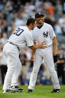 NEW YORK, NY - SEPTEMBER 19:  Jorge Posada #20 of the New York Yankees pushes his teammate Mariano Rivera #42 back towards the mound after Rivera broke the career saves record in a game against the Minnesota Twins at Yankee Stadium on September 19, 2011 i