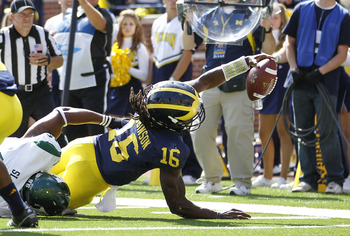 ANN ARBOR, MI - SEPTEMBER 17:  Denard Robinson #16 of the University of Michigan Wolverines stretches for the goal line during the second quarter of the game against Eastern Michigan Eagles at Michigan Stadium on September 17, 2011 in Ann Arbor, Michigan.