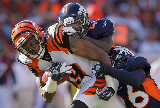 DENVER, CO - SEPTEMBER 18:  Wide receiver Jerome Simpson #89 of the Cincinnati Bengals makes a 31 yard pass reception as Cassius Vaughn #41 and Rahim Moore #26 of the Denver Broncos make the tackle in the third quarter at Sports Authority Field at Mile Hi