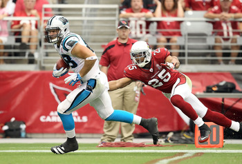 GLENDALE, AZ - SEPTEMBER 11:  Tight end Greg Olsen #88 of the Carolina Panthers runs with the football past Kerry Rhodes #25 of the Arizona Cardinals during the NFL season opening game at the University of Phoenix Stadium on September 11, 2011 in Glendale